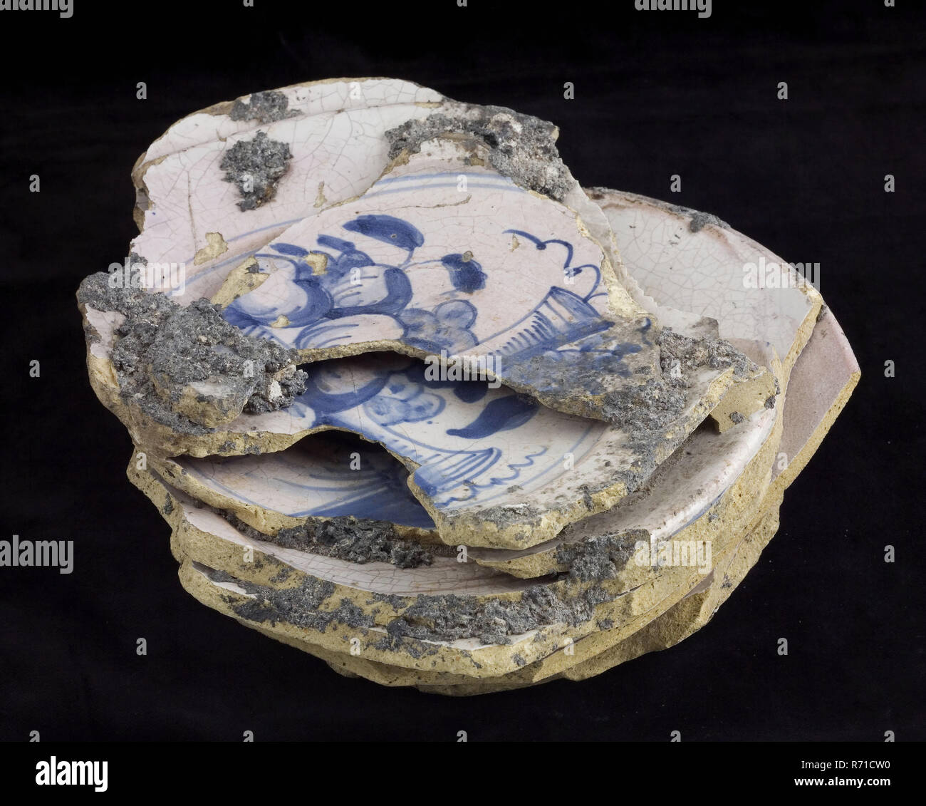Stack of nine faience plates, baked misbakels with fruit as decor, plate crockery holder soil find ceramic earthenware enamel tinglage, hand turned fried glazed decorated baked Pile of miscandes. Faience plates or delft pottery. Yellow shard entirely covered with tin glaze Decorated in blue on white fond decoration consists of two blue circles in the shoulder and in the mirror vase in the middle of fruit. Stand surface Only slanted sides at the bottom shoulder at the top between mirror and flag. Baked earthenware. Misbaksels: the plates are broken and melted together. Discoloration of enamel a - Stock Image