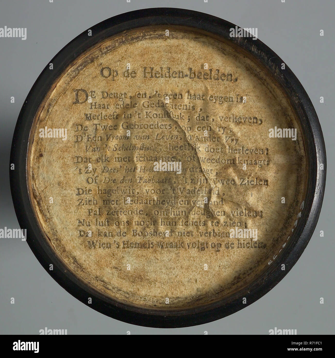 One-sided wooden medallion, covered with paper, with printed text OP DE HELDEN-BEELDEN , penny box holder of wood paper, Text, ON THE HERO-IMAGES THE DEUGT AND 'NO NONE OF ITS EYGEN IS HER EDELE THOUGHT; RELAXING IN THE KING; THAT THE TWO BROTHERS ON RY D HAS RAPIDLY RAPTLED FATH OF LIFE D 'OTHER VRY VAN' T SCHELMSTUCK; THAT EVERYTHING WITH SHEEP OR WEEDOM COMES 'T ZY DEES' WEARS THE HEART-WEAPON OR THAT TABLETS ITS TWO SOULS WHICH SHALL TAKE HAIL WHITE FOR THE FATHER'S COUNTRY WITH FAMILY AND REALIZING THEIR VIRTUES; NOW DOES NOT LIKE TO SEE THEIR SKETCH; THAT CAN NOT VOID THE BOOSHEYD WHEN H - Stock Image