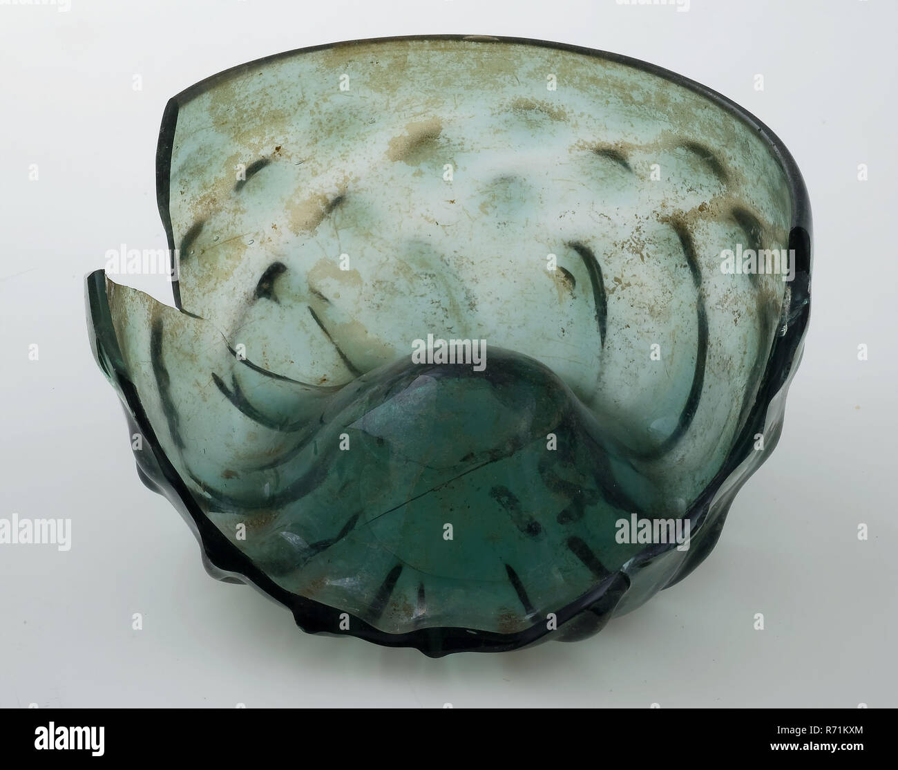 Fragment of low drinking glass with crossed rib pattern, maigelein, maigelein drinking glass drinking utensils tableware holder soil find glass of wood glass, in form blown glass application Fragment of low drinking glass maigelein in clear green glass (forest glass). Stuffed bottom with pontilemark and star pattern of twelve ridges continuous over wall. Wall decorated with crossed ribbed pattern that extends up to about 1.5 cm from annealed edge Minimal archeology iris serving drinking wine - Stock Image