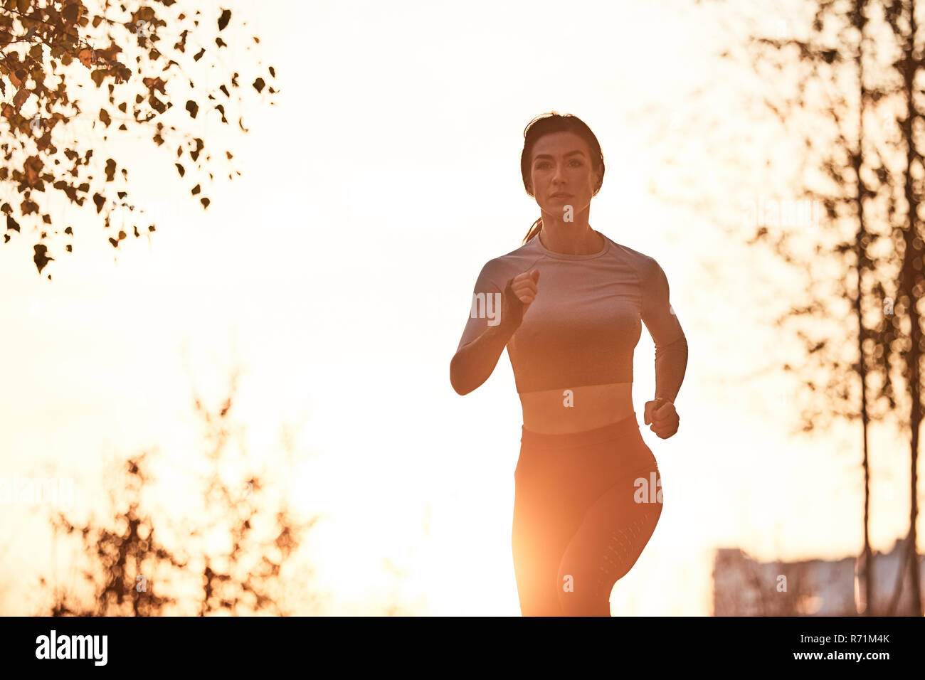 a lone female jogging in a city location - Stock Image