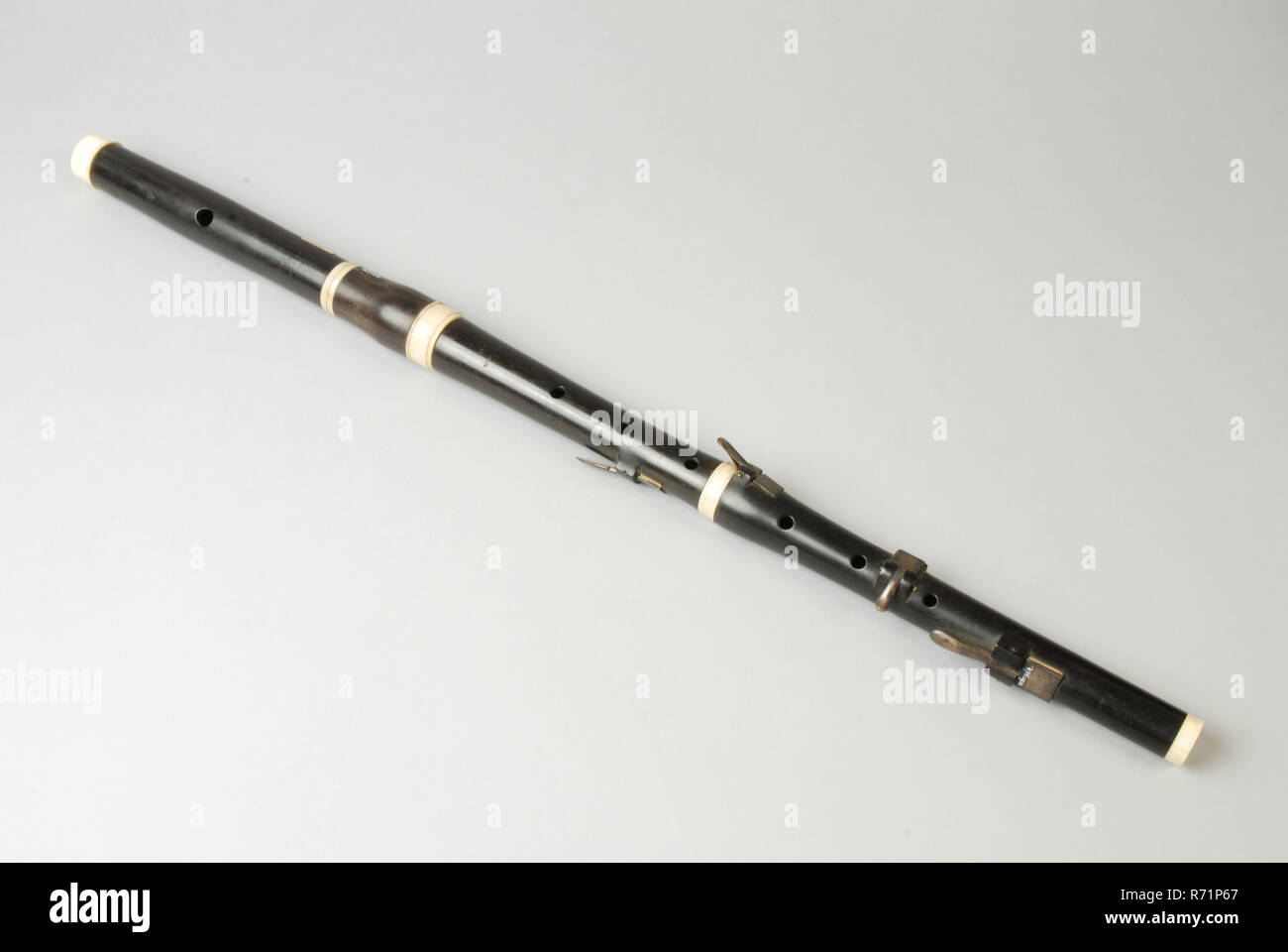 J. Mandt, Ebony flute in four parts, flute flute aerobic musical instrument acoustic wood ebony silver copper metal ivory, rotated drilled Wooden flute in four parts with ivory spacers The pedestal, has six tonalities, three of which are provided with silver flap: the flap at the bottom of the other two probably for half-tone distances The middle part, has four tone holes: three for the fingers plus tonal hole with flap Between the center piece and the mouth piece an extra piece is fitted without tone holes connecting the nozzle piece. The flute is marked on mouthpiece (C) and middle piece, Ma - Stock Image