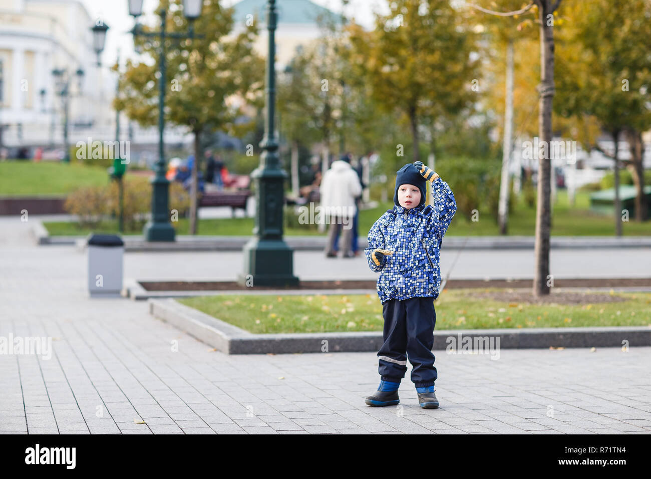 Handsome young boy walks in the area. Toddler thought. The child scratches his head and thinks. Children dream. - Stock Image