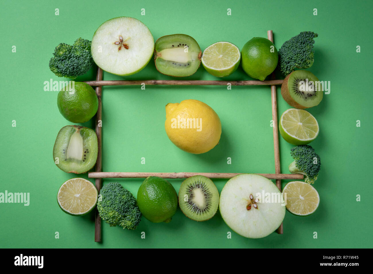 Yellow lemon fruit on green background in the middle of fresh fruits frame. Rich in vitamins food above view - Stock Image