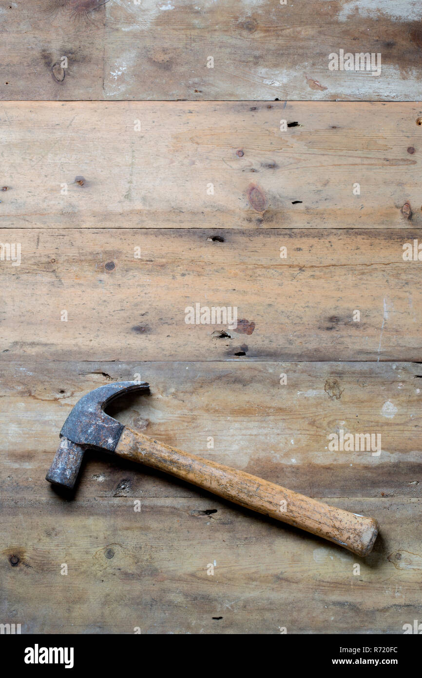 A wooden handled claw hammer on a rough wood surface. - Stock Image