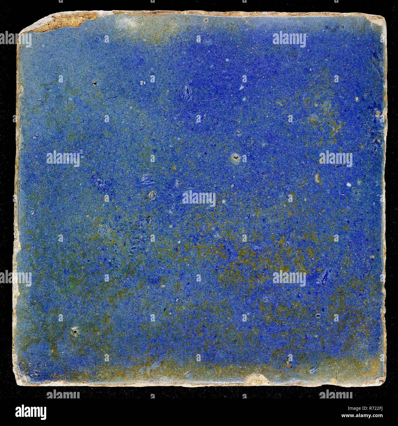 Plain blue floor tile or wall tile, wall tile? floor tile? tile sculpture ceramic earthenware glaze tin glaze, in shape made baked glazed painted baked Wall tile or floor tile. Orange-brown shard. Completely solid blue Possible iridescence in the glaze layer. Slanted sides of indigenous pottery - Stock Image