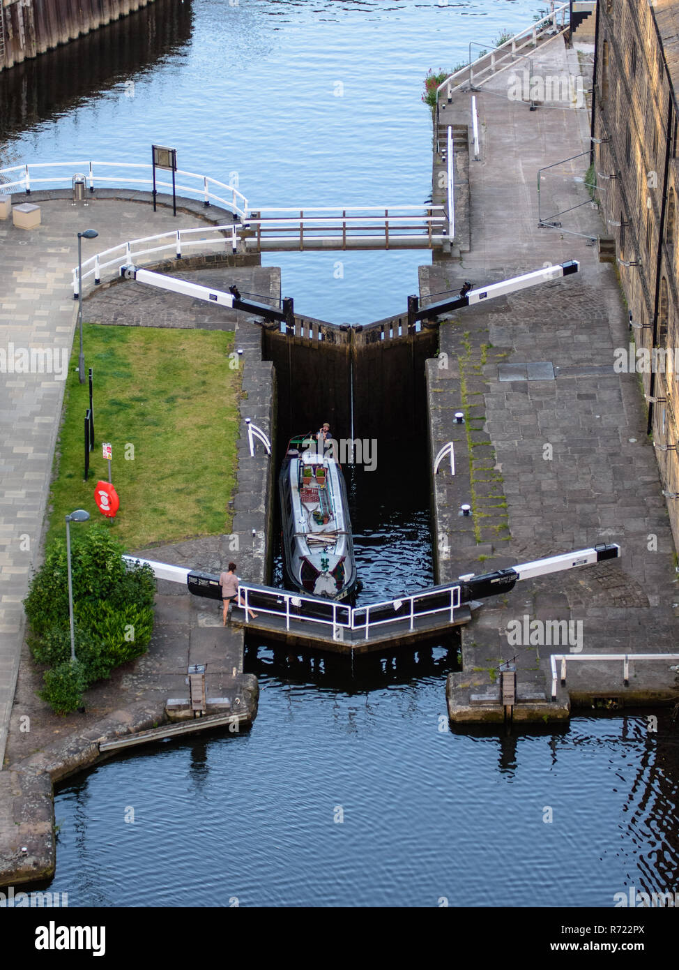 Leeds, England, UK - June 28, 2015: A couple navigate canal lock gates separating the River Aire navigation from the Leeds and Liverpool Canal as view - Stock Image
