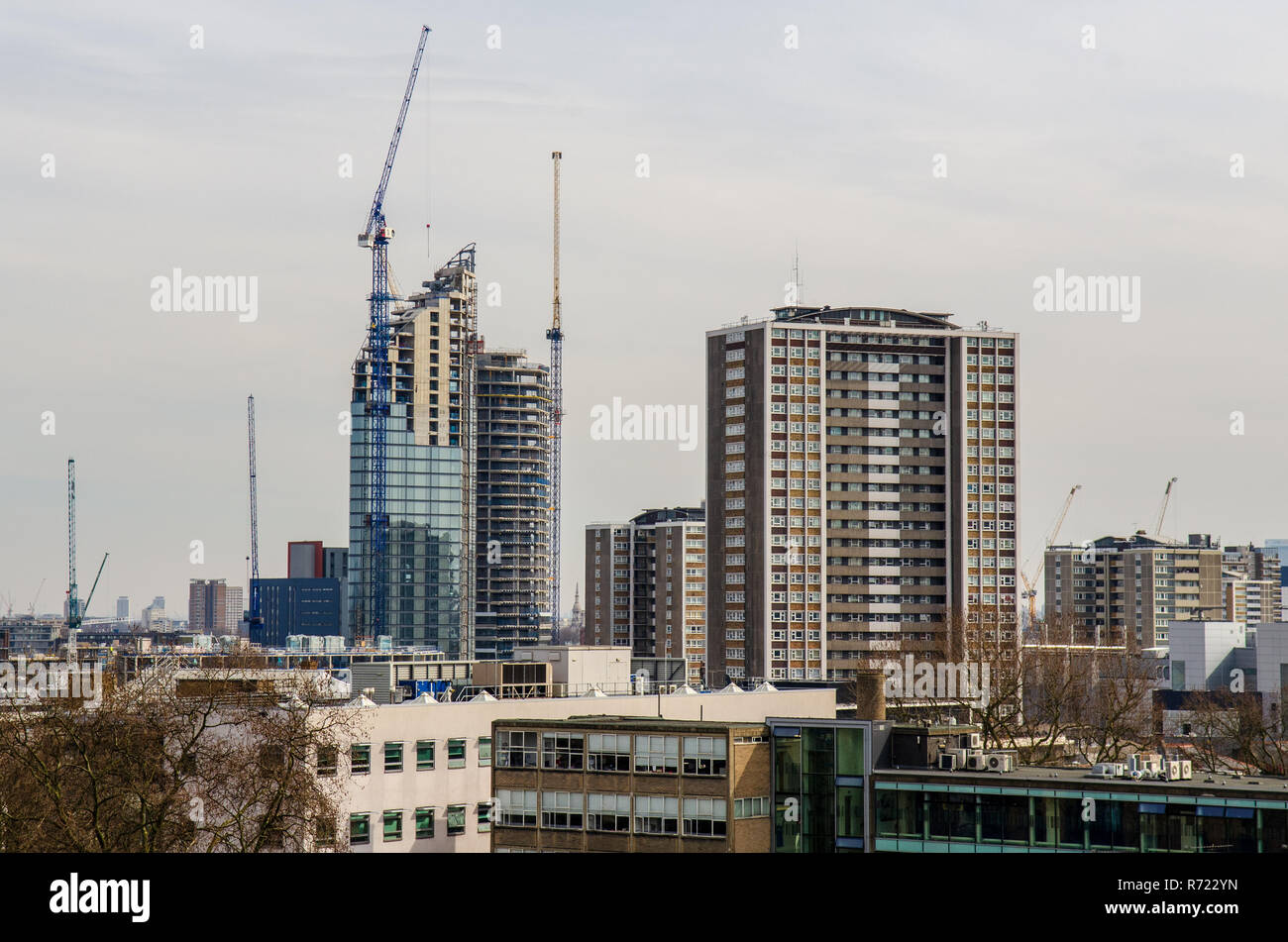 London, England, UK - March 13, 2015: Tower cranes stand over the construction sites of skyscrapers, part of a cluster of new-build high-rise apartmen - Stock Image