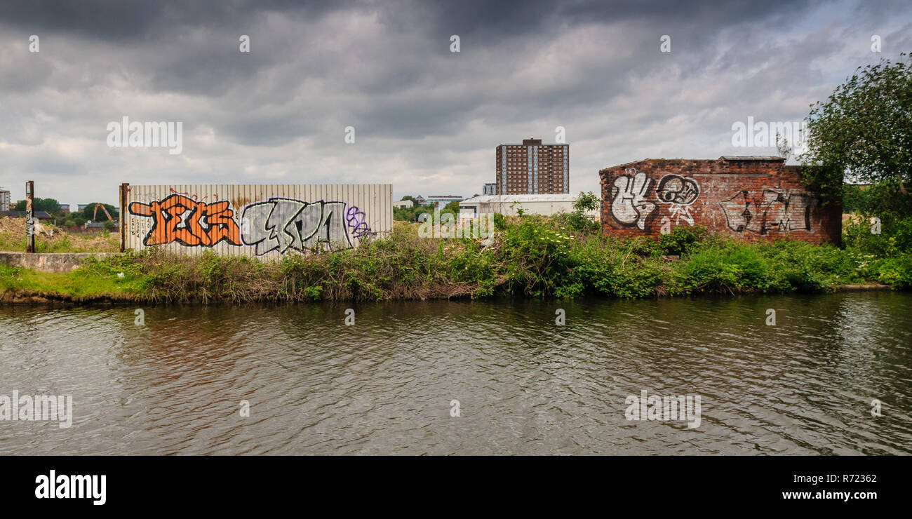 Manchester, England, UK - May 21, 2011: Derelict wasteland awaits redevelopment alongside the Bridgewater Canal at Pomona Strand in Manchester, with h - Stock Image