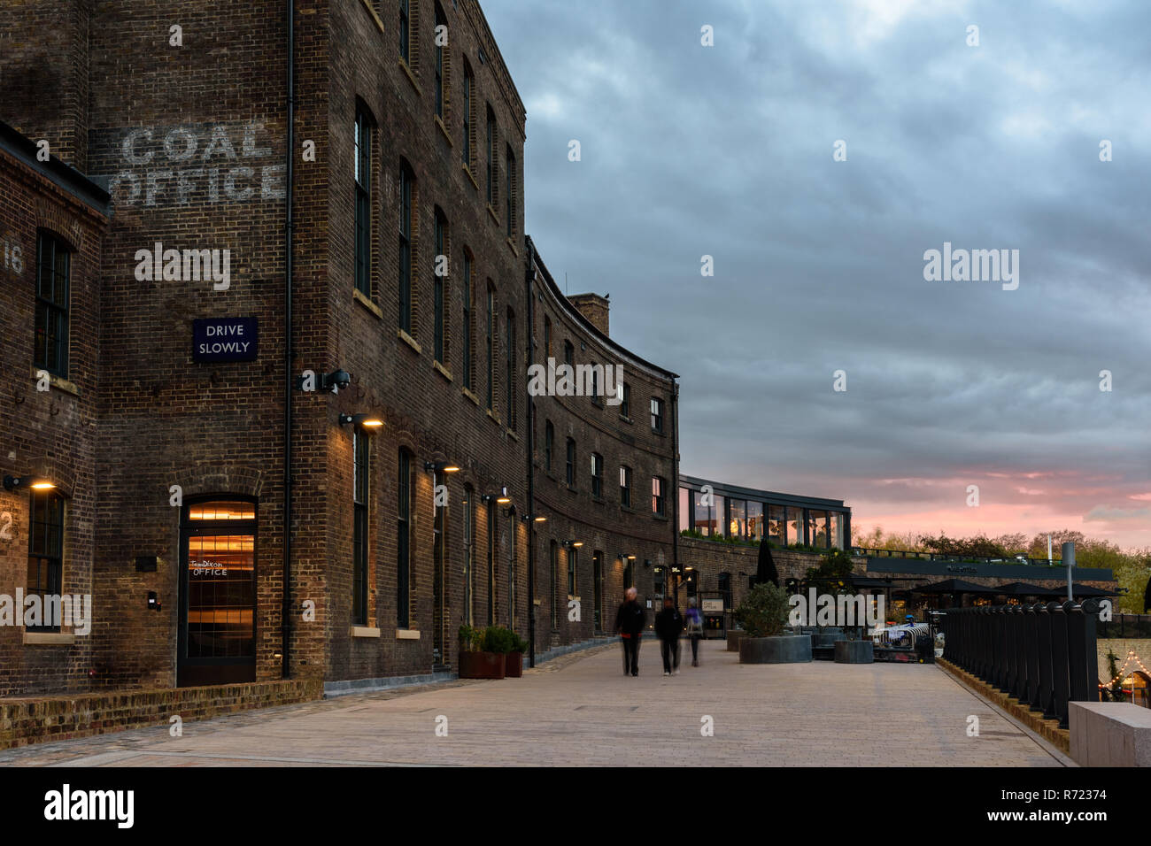 London, England, UK  November 21, 2018: The sun sets behind the Victorian brick Coal Office, once part of the King's Cross railway work and now a shop - Stock Image