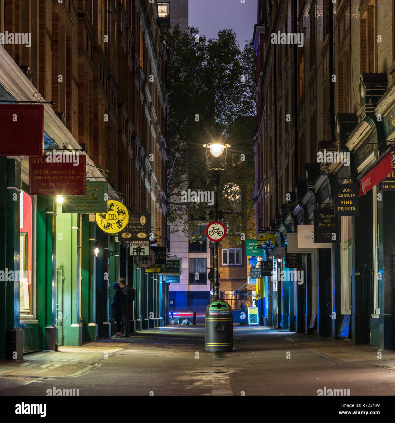 London, England, UK - October 15, 2018: Pedestrians browse traditional shop windows on the pedestrianised Cecil Court street, off Charing Cross Road i - Stock Image