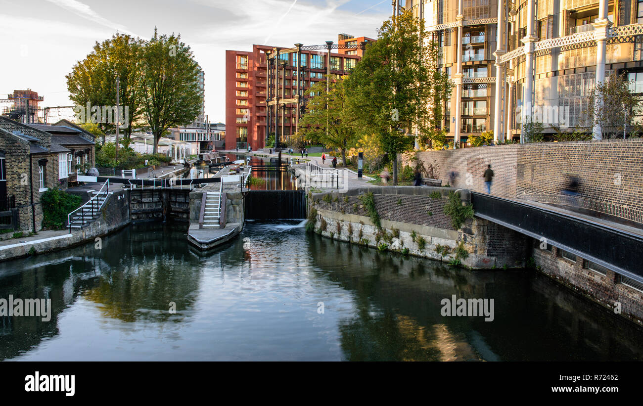 London, England, UK - September 24, 2018: Pedestrians and cyclists travel along the Regent's Canal towpath at St Pancras Lock, beside Gasholders Park  - Stock Image