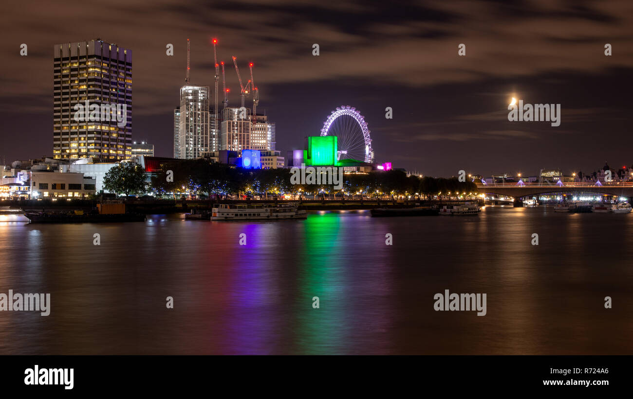 London, England, UK - September 14, 2018: A cluster of tower cranes are lit at night over the Shell Centre construction site beside the London Eye on  - Stock Image