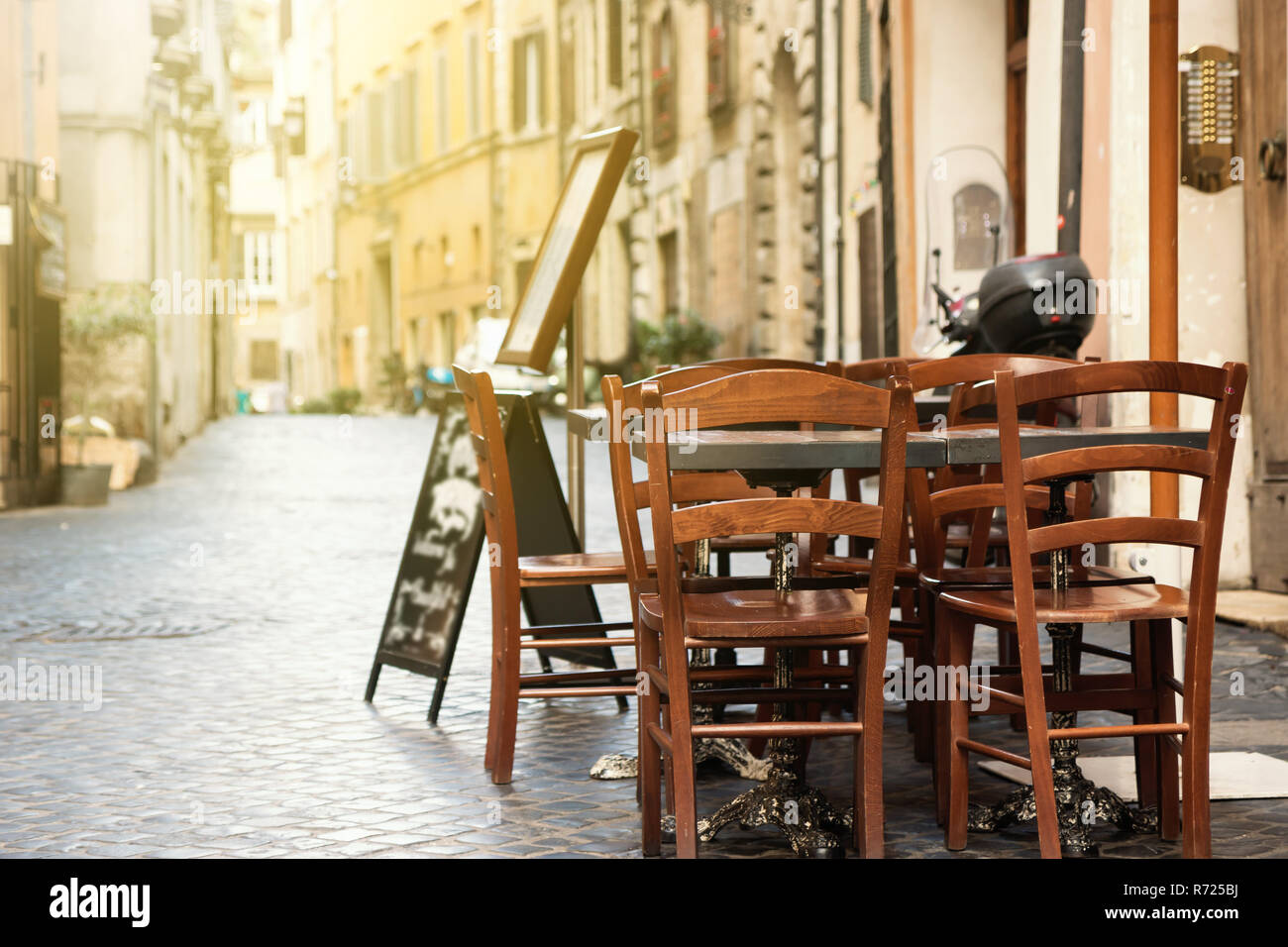 Empty Dining Table With Chairs Is Standing In A Street Lit By Morning Sunlight