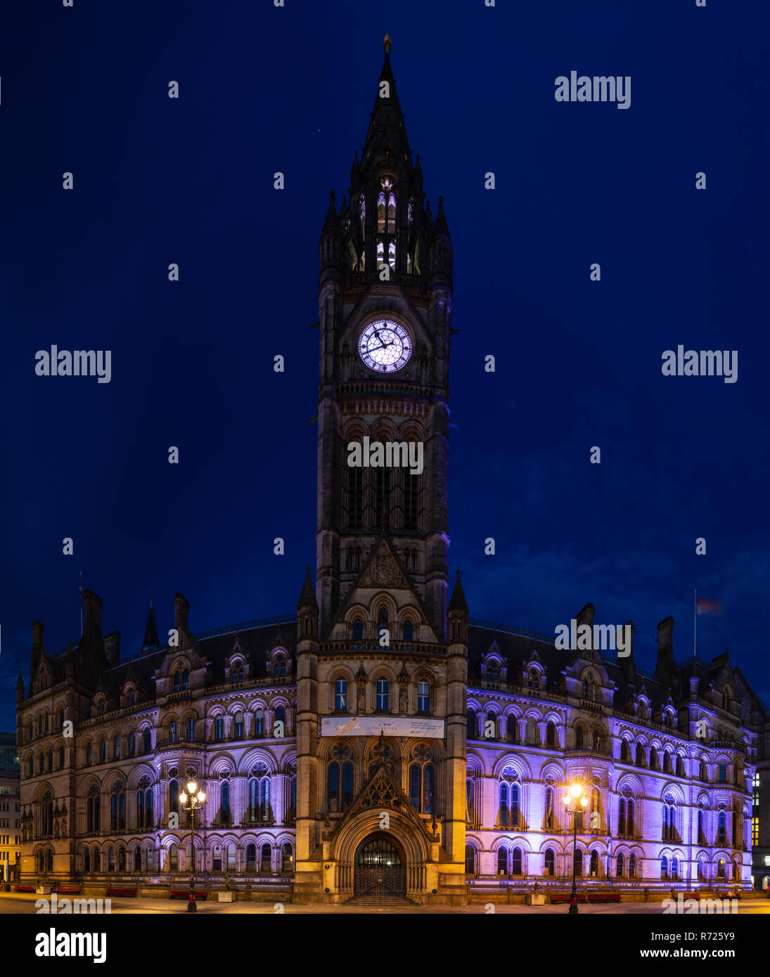 Manchester, England, UK - July 1, 2018: The gothic exterior and clock tower of Manchester Town Hall is lit at night on the city's Albert Square. - Stock Image