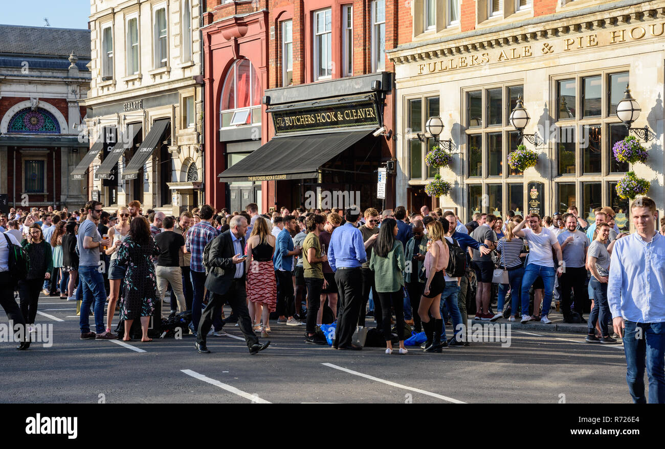 London, England, UK - April 20, 2018: Crowds of after-work drinkers socialise outside pubs and bars near Smithfield Market in the City of London on a  - Stock Image