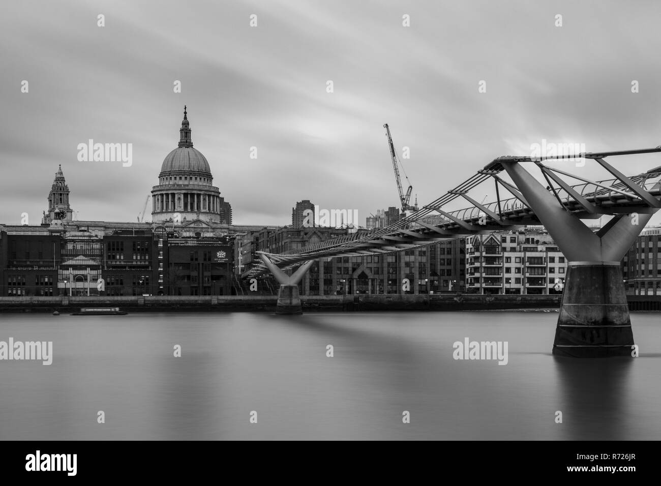 London, England, UK - April 3, 2018: The River Thames flows under London's Millennium Bridge, with St Paul's Cathedral and office blocks of the City f - Stock Image