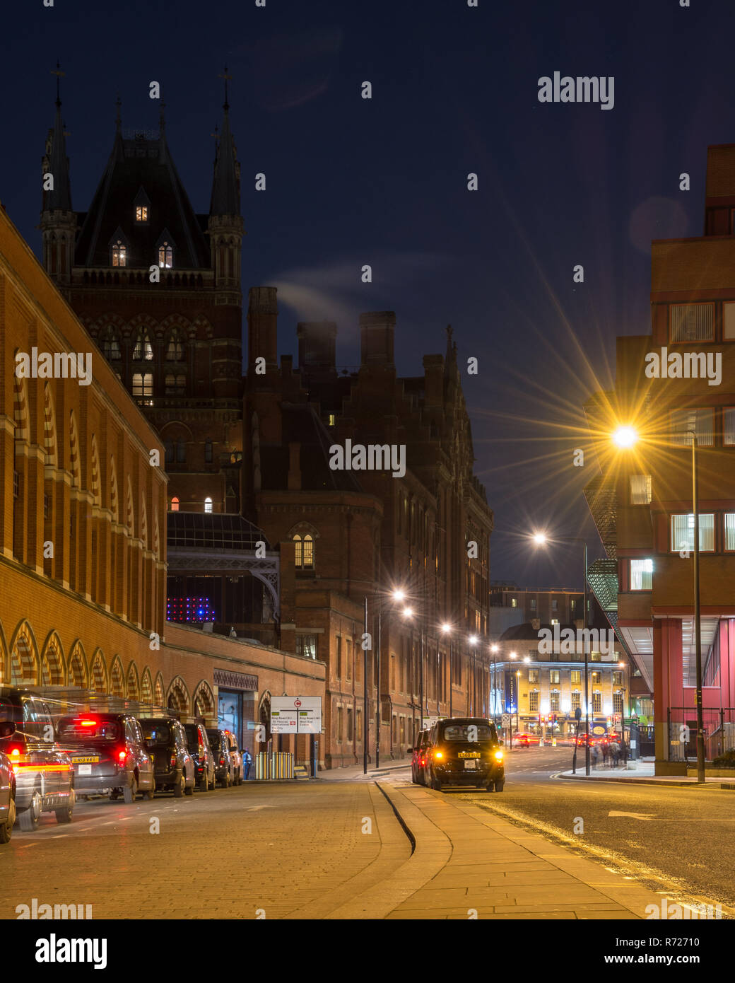 London, England, UK - February 27, 2018: Taxis queue at a rank outside London's ornate Victorian gothic brick St Pancras Railway Station  at night. - Stock Image