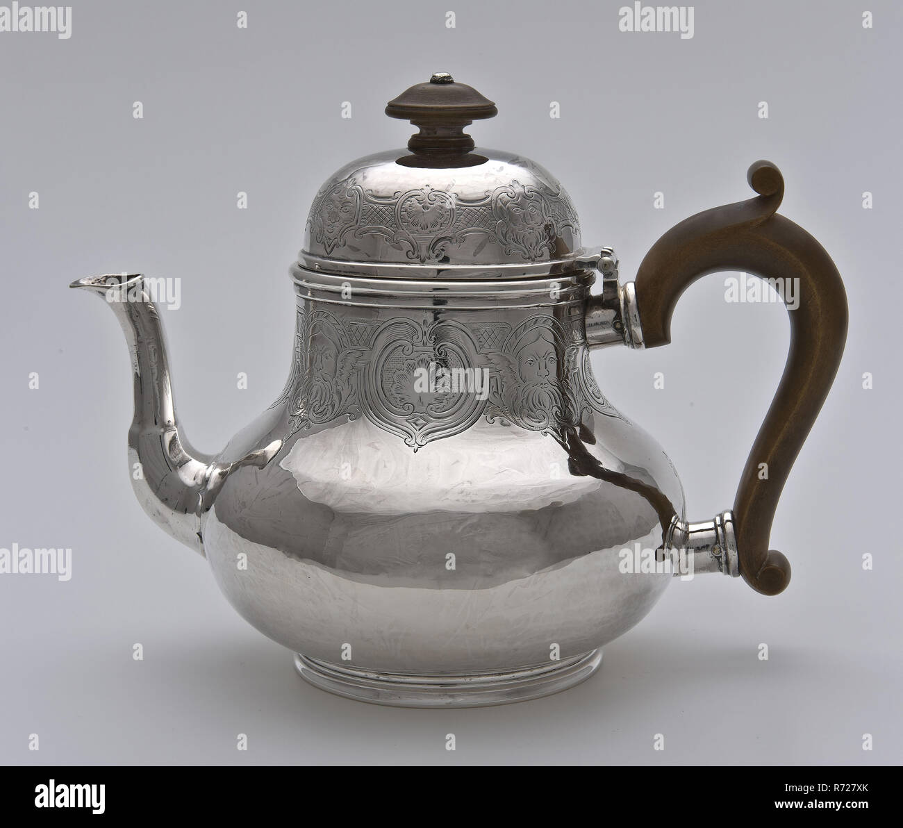 Silver teapot with brown wooden handle in bud on lid, teapot tableware holder silver wood, engraved pear shaped body on constricted stand ring high arched lid with hinge spout wooden thorned ear wooden buttoned button bottom bottom (smashed) serve serve tea drink drink tea set - Stock Image