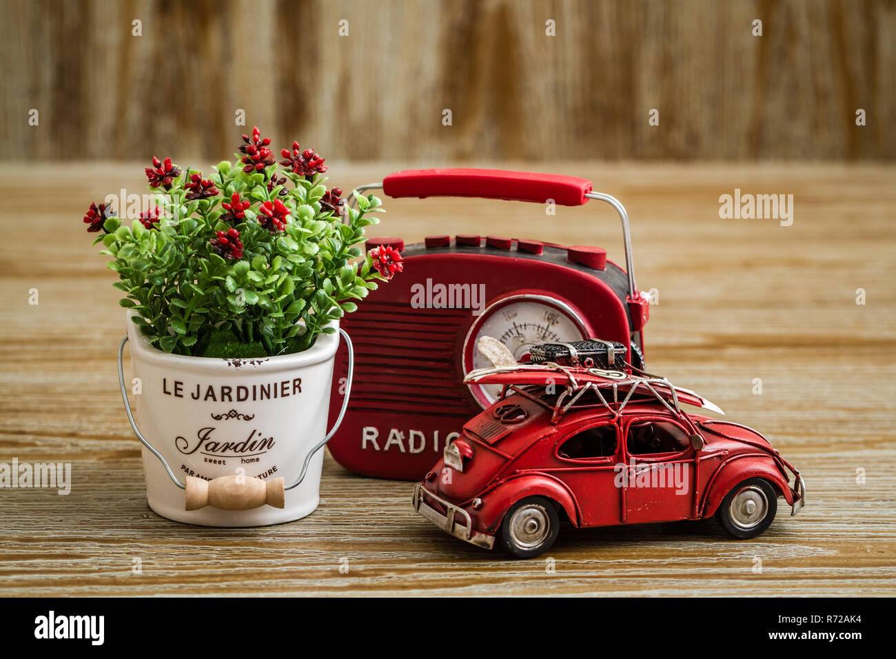 Artificial Flower, Vintage Radio and Red Toy Car on Wooden Background Stock Photo