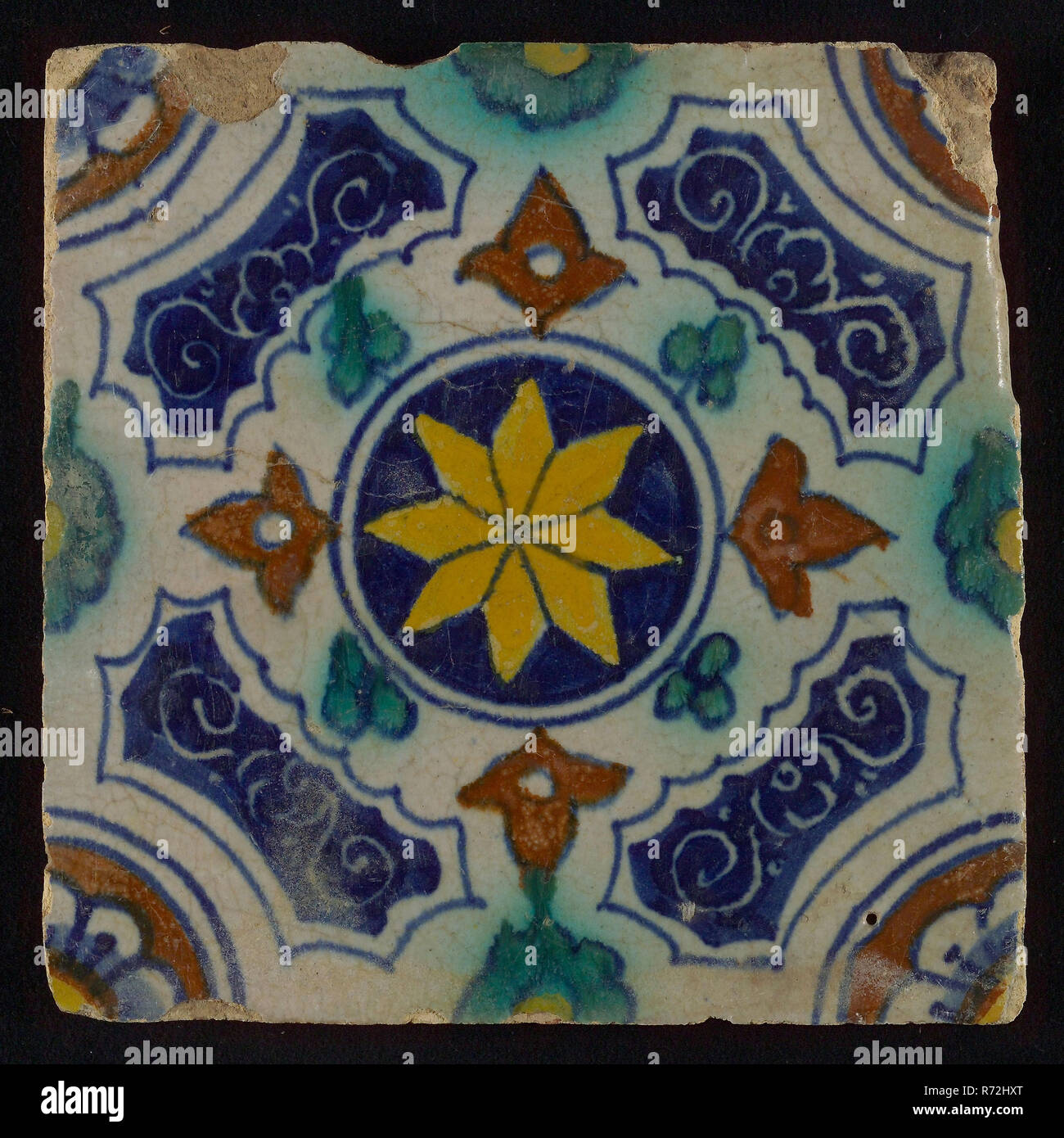 Tile, blue, green, brown and yellow on white, central yellow star in circle, sgraffito surfaces, corner motif, quarter rosette, wall tile tile sculpture ceramic earthenware glaze, baked 2x glazed painted Yellow - red shard square bevelled sides. Two or four nail holes. AIb3. - Stock Image
