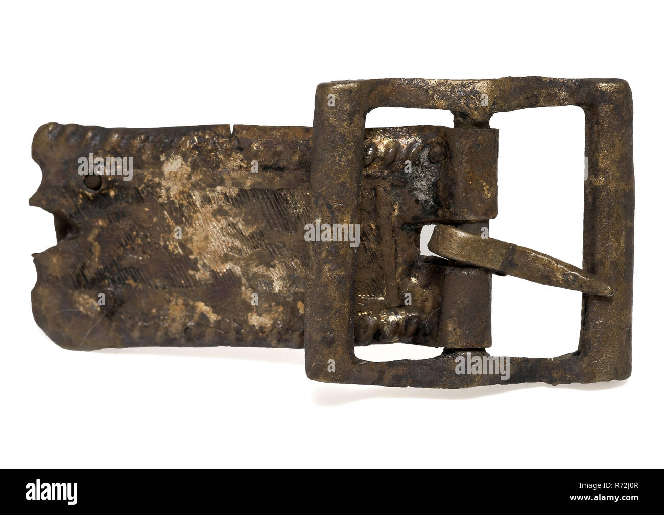 Brass buckle, rectangular and processed leather fitting, buckle fastener part soil find brass metal, with handle molded engraved Buckle with rectangular bow and middle post Around the middle post an elongated decorated piece of leather furniture The decoration consists of twine decor along the perimeter in the middle field with arches left in hatching poorly identifiable archeology Rotterdam rail tunnel attaching fasten garments Soil discovery: trajectory Rotterdam rail tunnel. Stock Photo