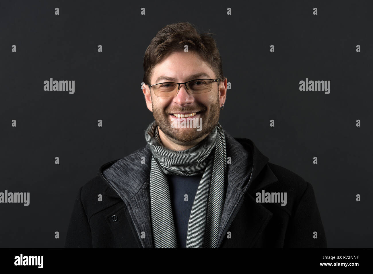 Bearded man in scarf and coat on dark background. Happy man in glasses on bearded face. Fashion model with beard smile on dark background. Autumn style and trend. Fashion accessory concept. - Stock Image
