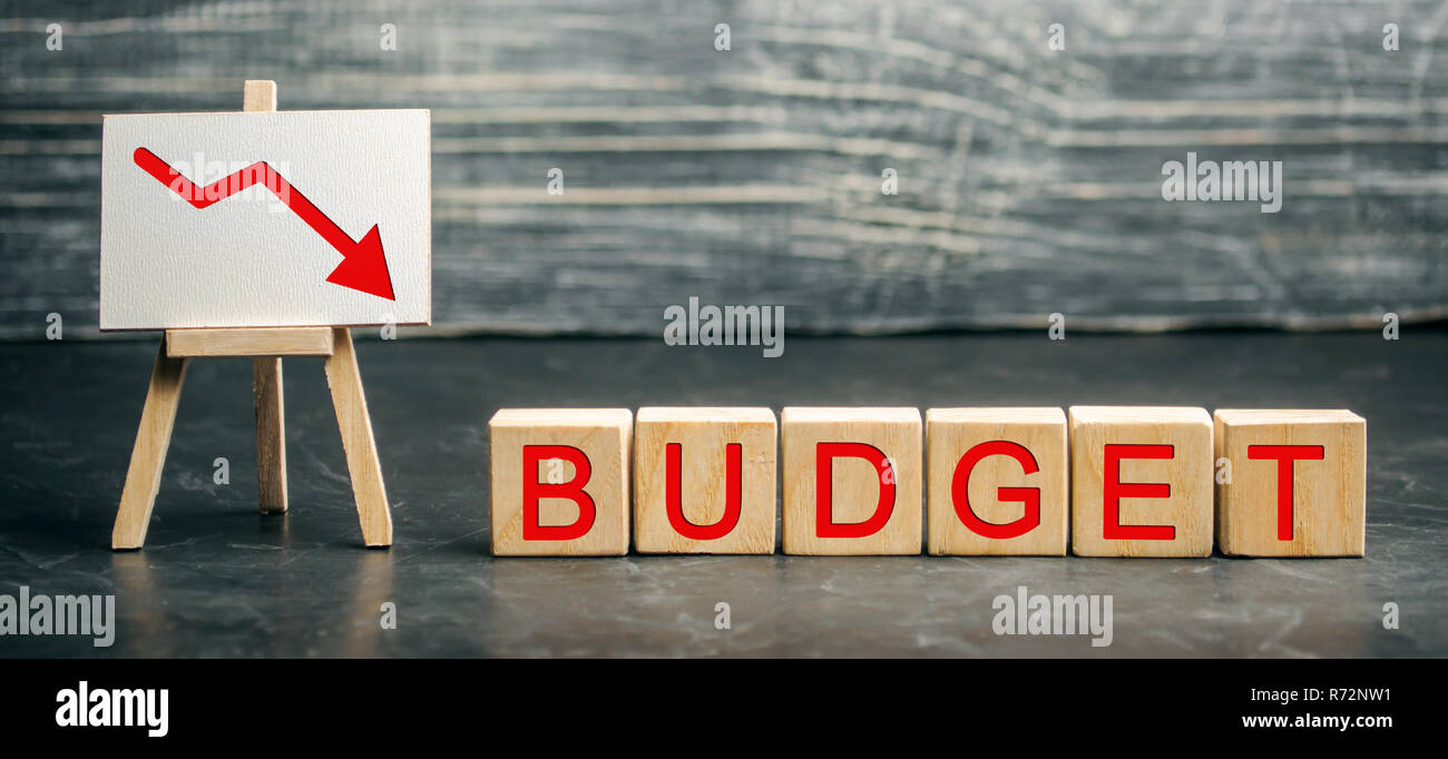 Wooden blocks and the inscription Budget and the arrow down. Unsuccessful business and poverty. Profit decline. Loss of investment. Low wages and savi - Stock Image