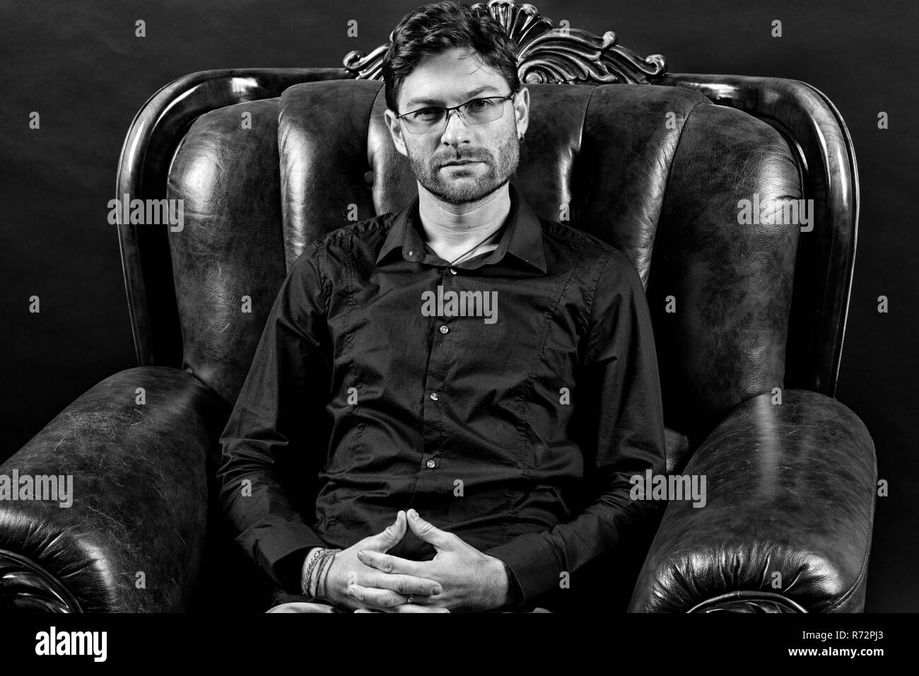 Bearded man relax in leather armchair. Man with beard on unshaven face. Macho wear shirt and glasses. Barber salon and skincare. Fashion accessory and furniture, black and white. - Stock Image