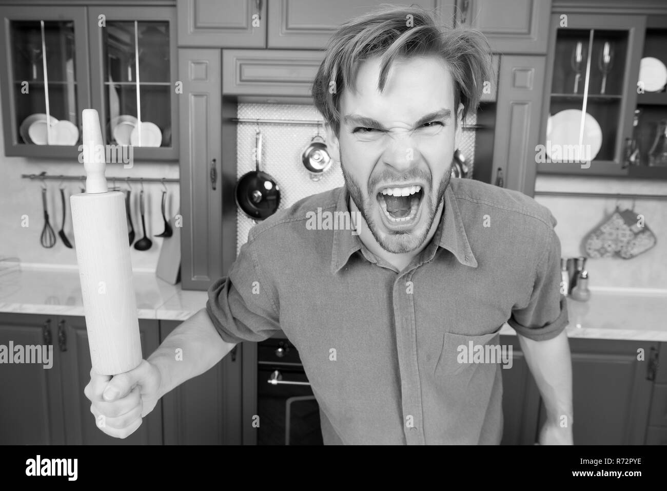 Man with angry face shout with rolling pin in kitchen. Cook, bake, home food concept - Stock Image
