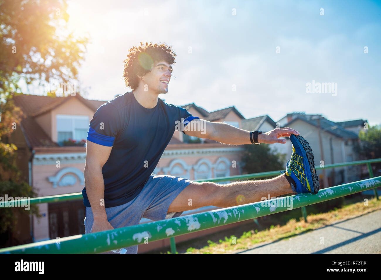 Smiling fitness man doing stretching exercise, preparing for workout in the park Stock Photo