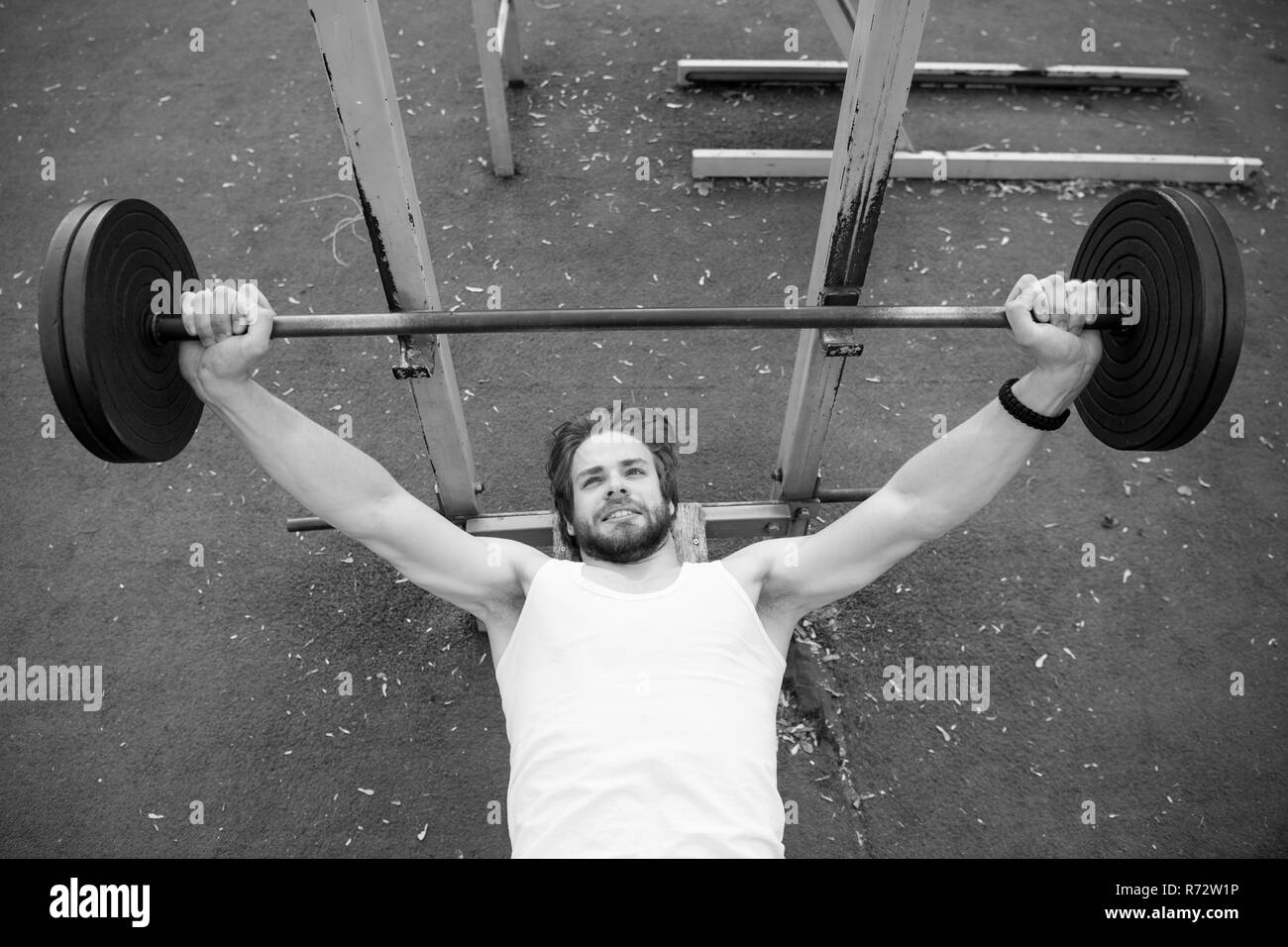 Weightlifting, bodybuilding, fitness, sport. Bodybuilder lift barbell on stadium. Man with athletic torso, strong arms training with weight. Power, energy, strength concept - Stock Image