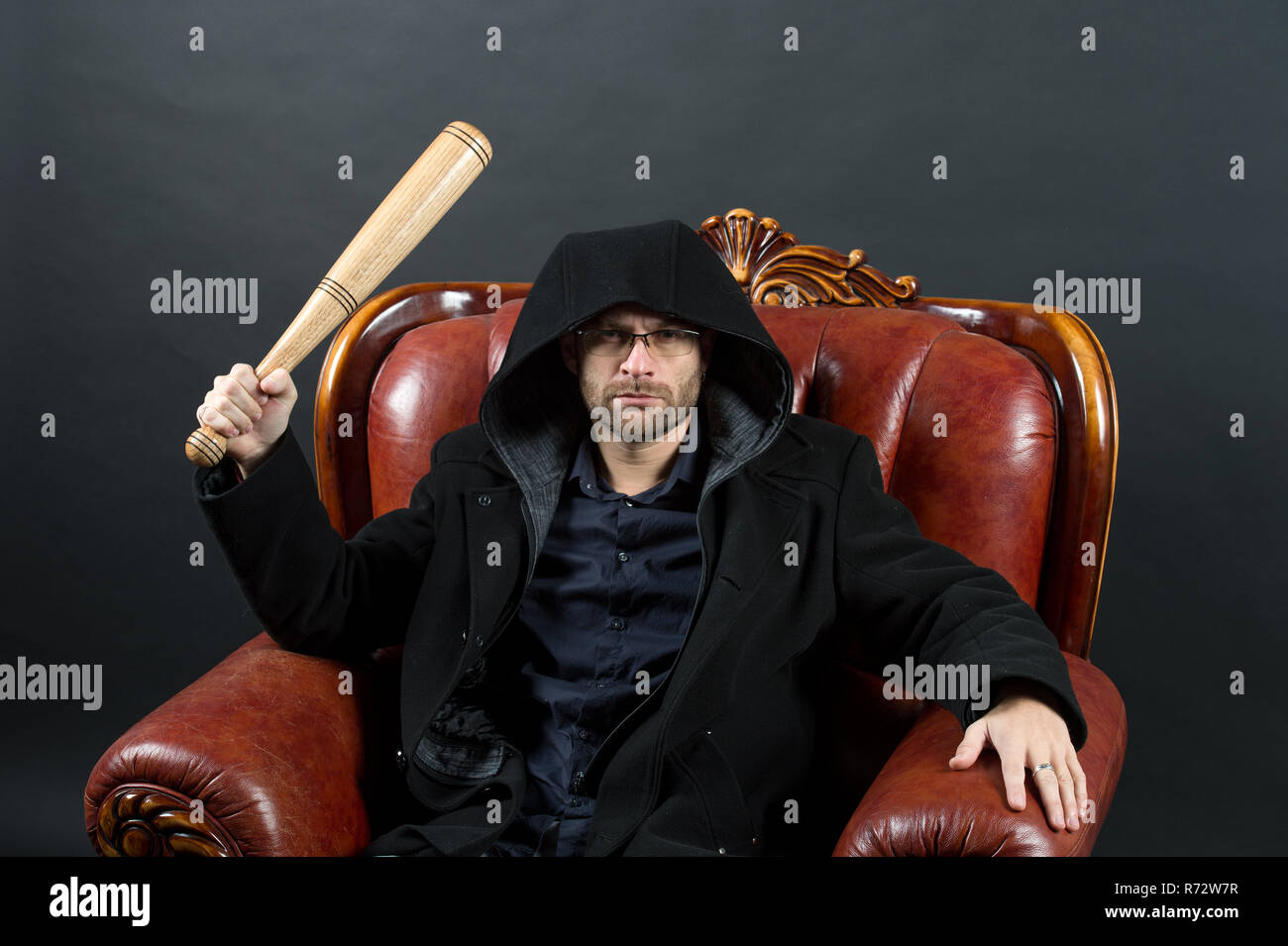 Crime or aggression and violence concept. Bearded man with baseball bat sit in armchair. Criminal wear hood in coat. Gangster guy strike with bat weapon. - Stock Image
