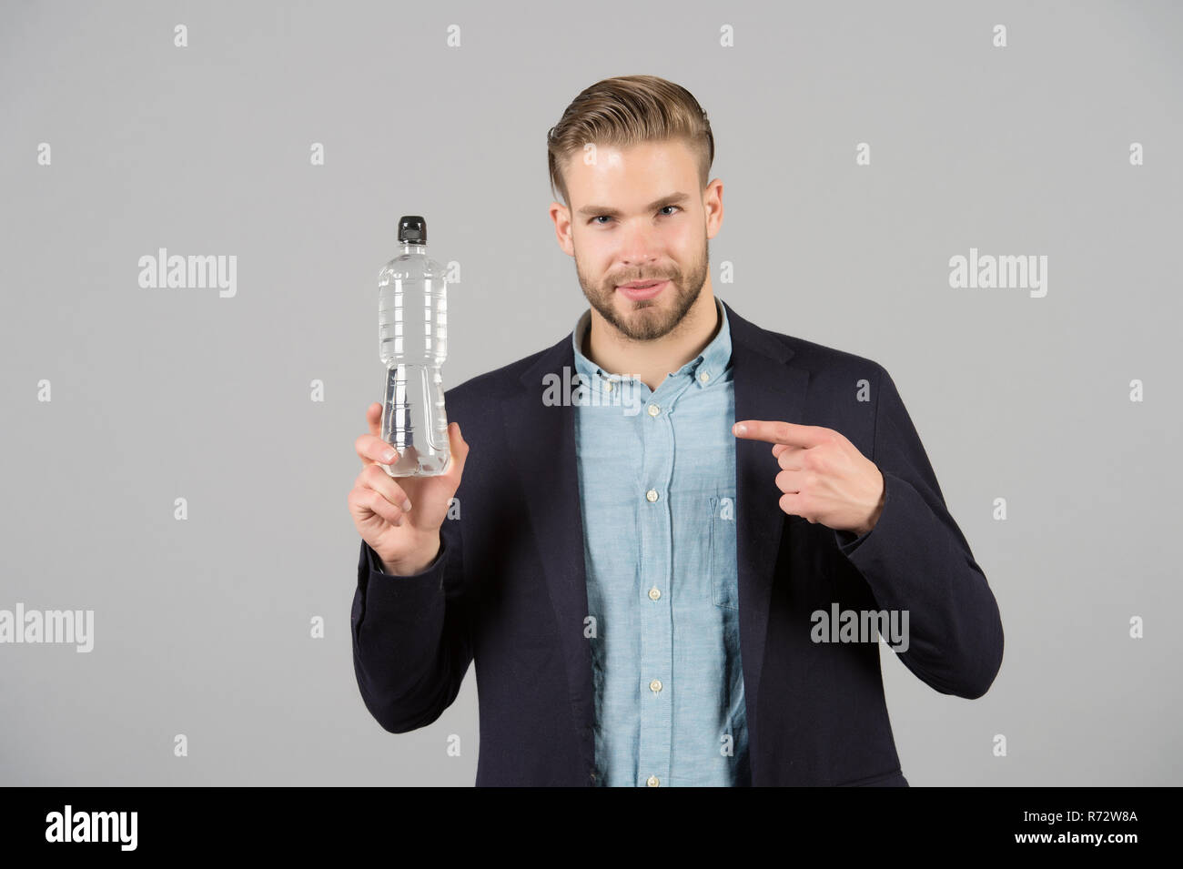 Man point finger at plastic bottle. Thirsty man with water bottle. Thirst and dehydration. Drinking water for health. Presenting product concept. - Stock Image