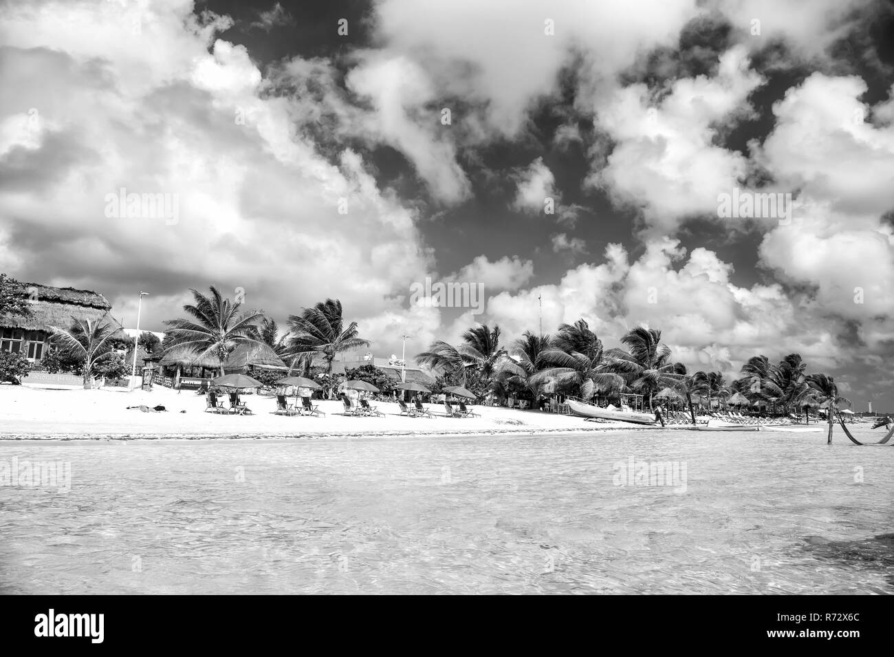 Beach with green palm trees, umbrellas on sand. Sea or ocean water at Costa Maya, Mexico. Tropical resort on sunny day on cloudy blue sky. Summer vacation, travelling concept. - Stock Image