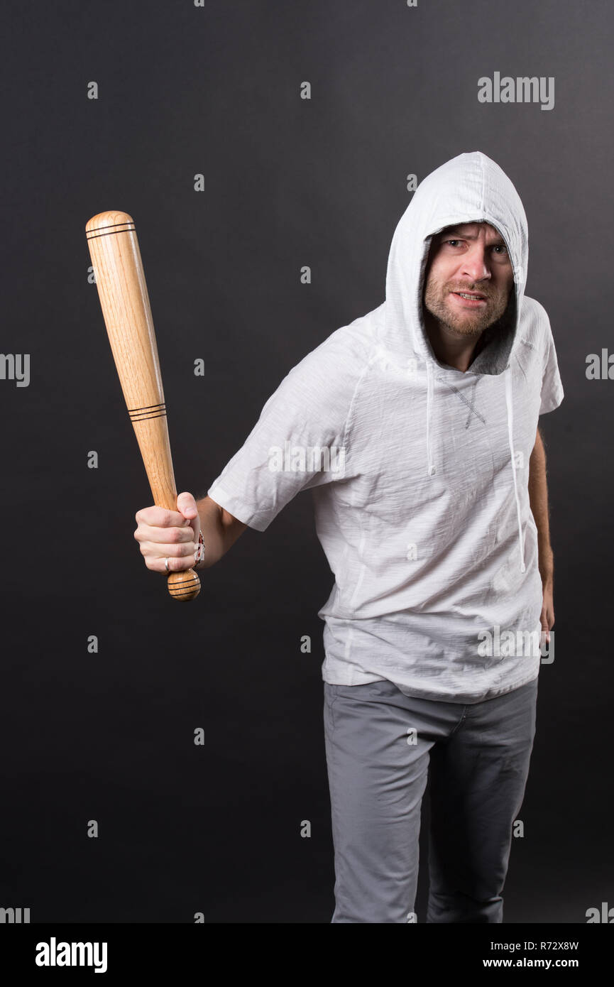 Bearded man hold baseball bat. Hooligan wear hood in hoodie tshirt. Gangster guy threaten with bat weapon. Aggression or anger and violence concept. - Stock Image