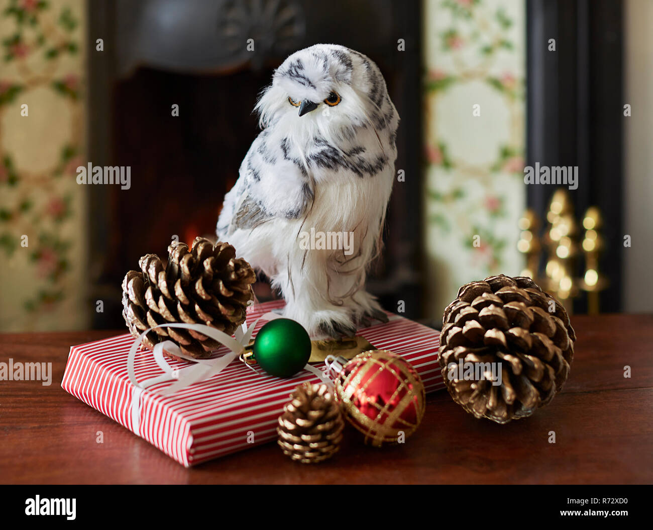 Snow owl and Christmas present with Christmas bubbles and acorns - Stock Image