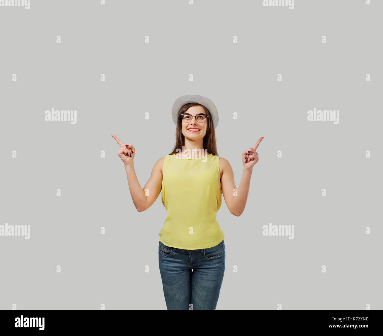 Casual woman pointing up - Stock Image
