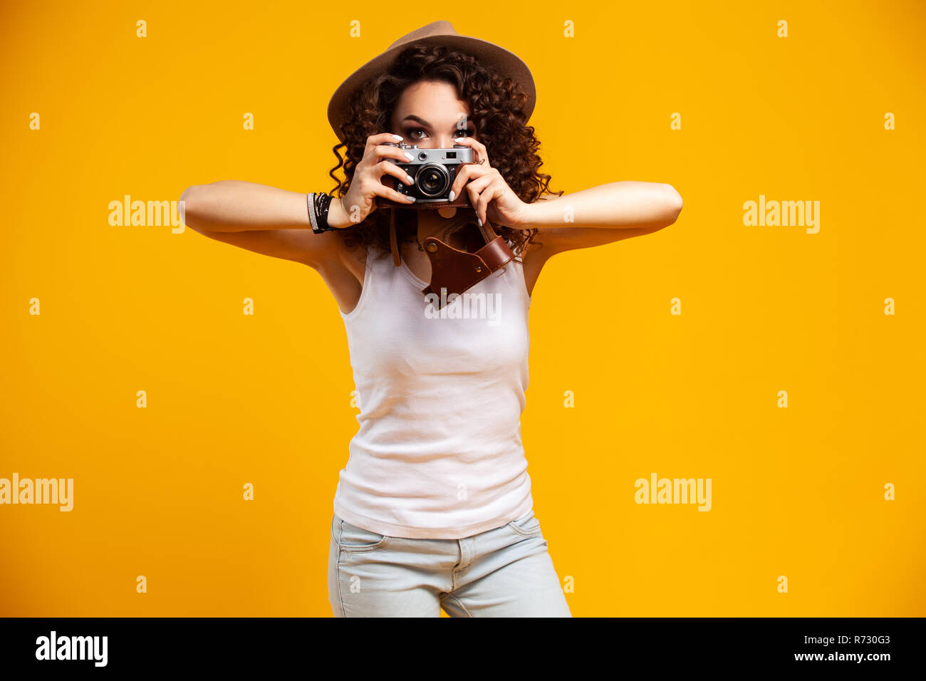 Portrait of laughing young woman taking pictures on retro vintage photo camera isolated on bright yellow background. People sincere emotions, lifestyl - Stock Image