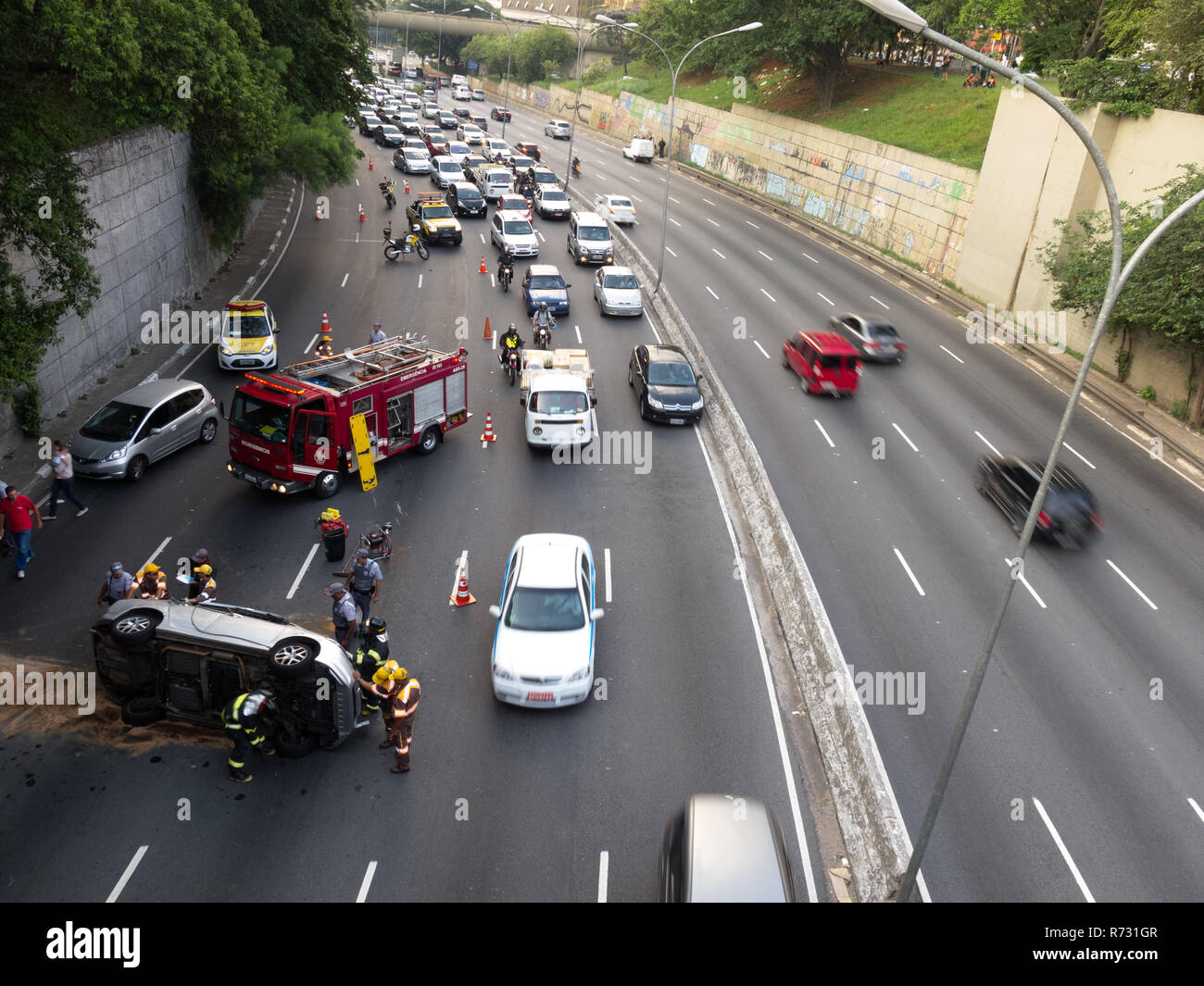 Extrication scene, firefighters and 'Traffic Engineering Company (CET)' at the car rollover accident scene, Av. 23 de Maio, Paraiso, Sao Paulo, Brazil Stock Photo