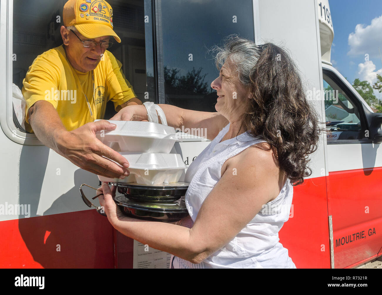A Southern Baptist Disaster Relief volunteer gives hot meals to a flood victim in Baton Rouge, Louisiana. - Stock Image