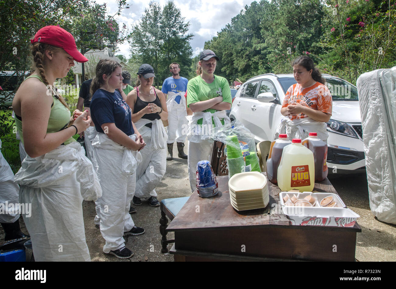 Student volunteers from Louisiana State University's Baptist Collegiate Ministry pray before eating lunch after a flood in Denham Springs, Louisiana. - Stock Image