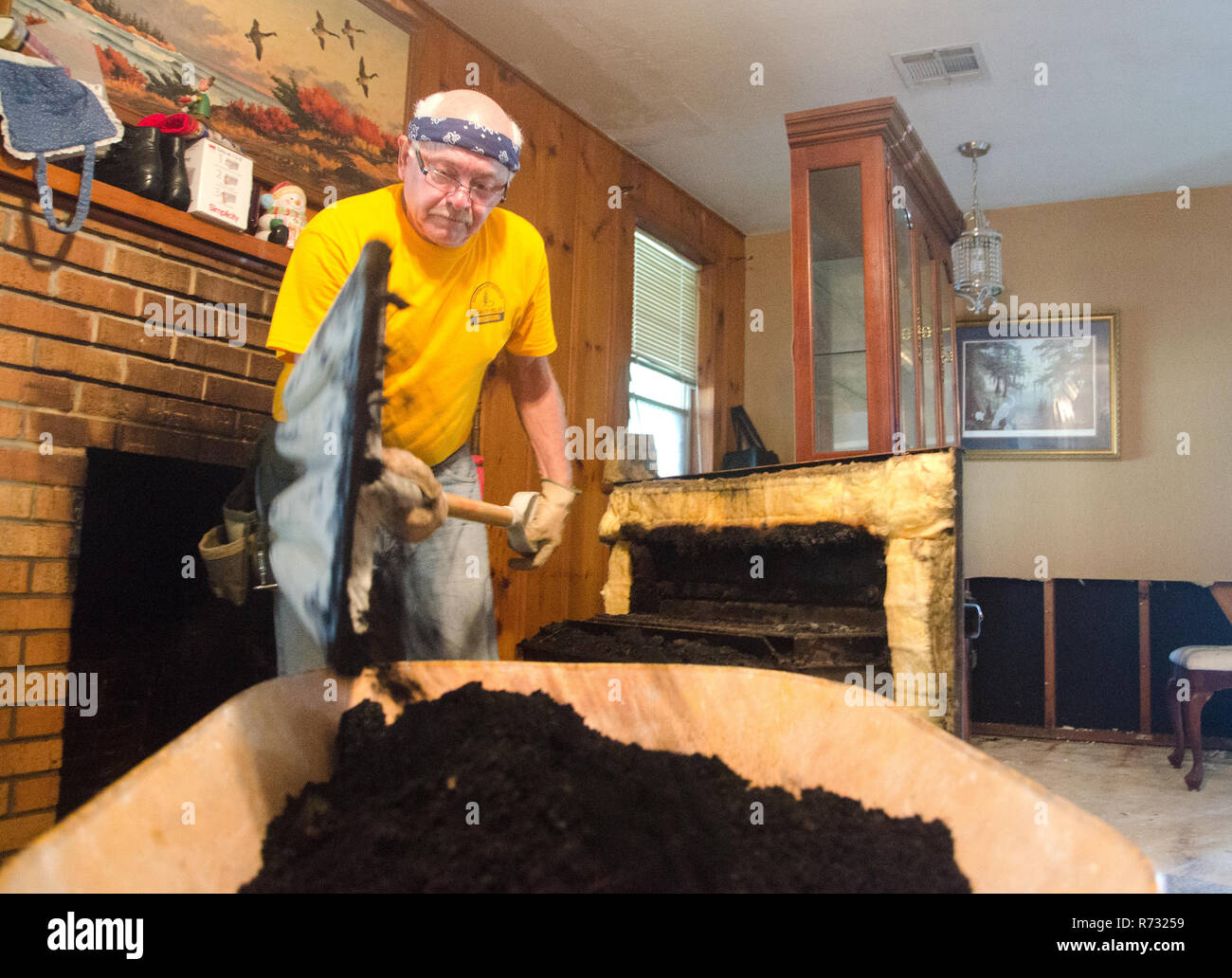 A Southern Baptist Disaster Relief volunteer shovels soot from a fireplace after a flood in Baton Rouge, Louisiana. - Stock Image