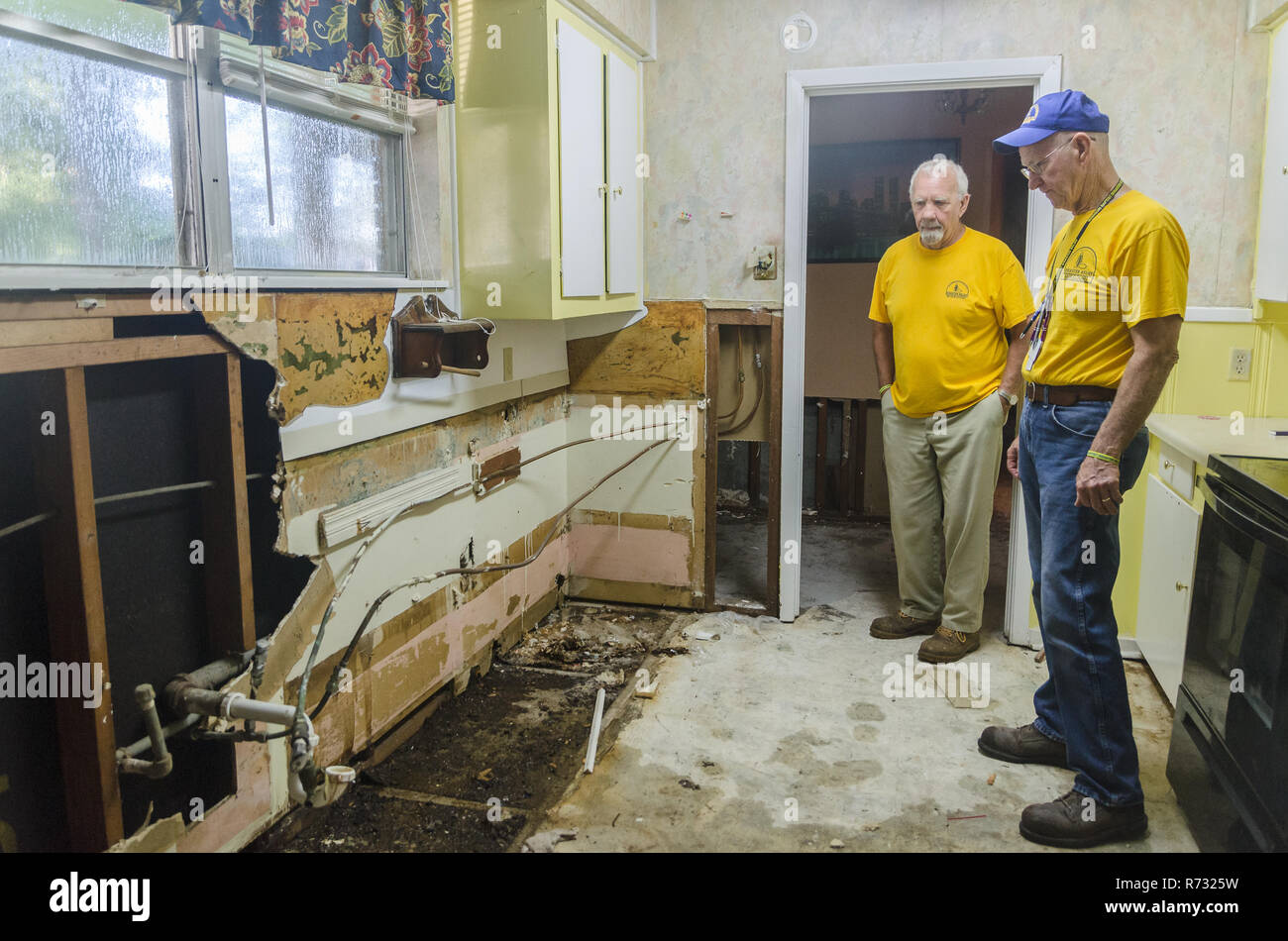 Southern Baptist Disaster Relief volunteers inspect a flood-damaged wall after a flood in Baton Rouge, Louisiana. Stock Photo