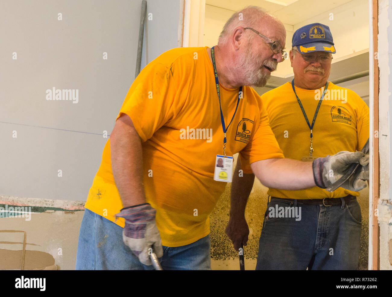 Southern Baptist Disaster Relief volunteers remove a damaged door frame from a flooded house after a flood in Baton Rouge, Louisiana. - Stock Image