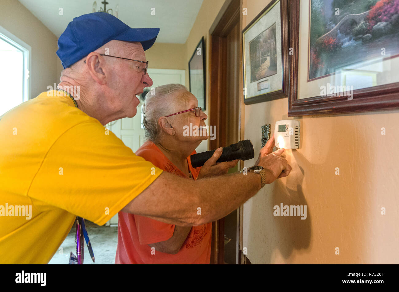A Southern Baptist Disaster Relief volunteer helps a flood victim set the thermostat in her house after a flood in Baton Rouge, Louisiana. - Stock Image