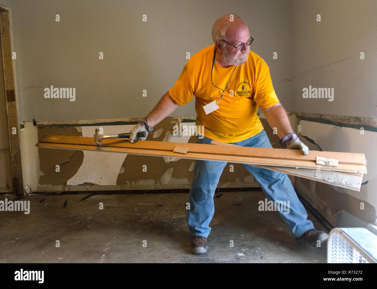 A Southern Baptist Disaster Relief volunteer removes damaged wood from a home after a flood in Denham Springs, Louisiana. - Stock Image