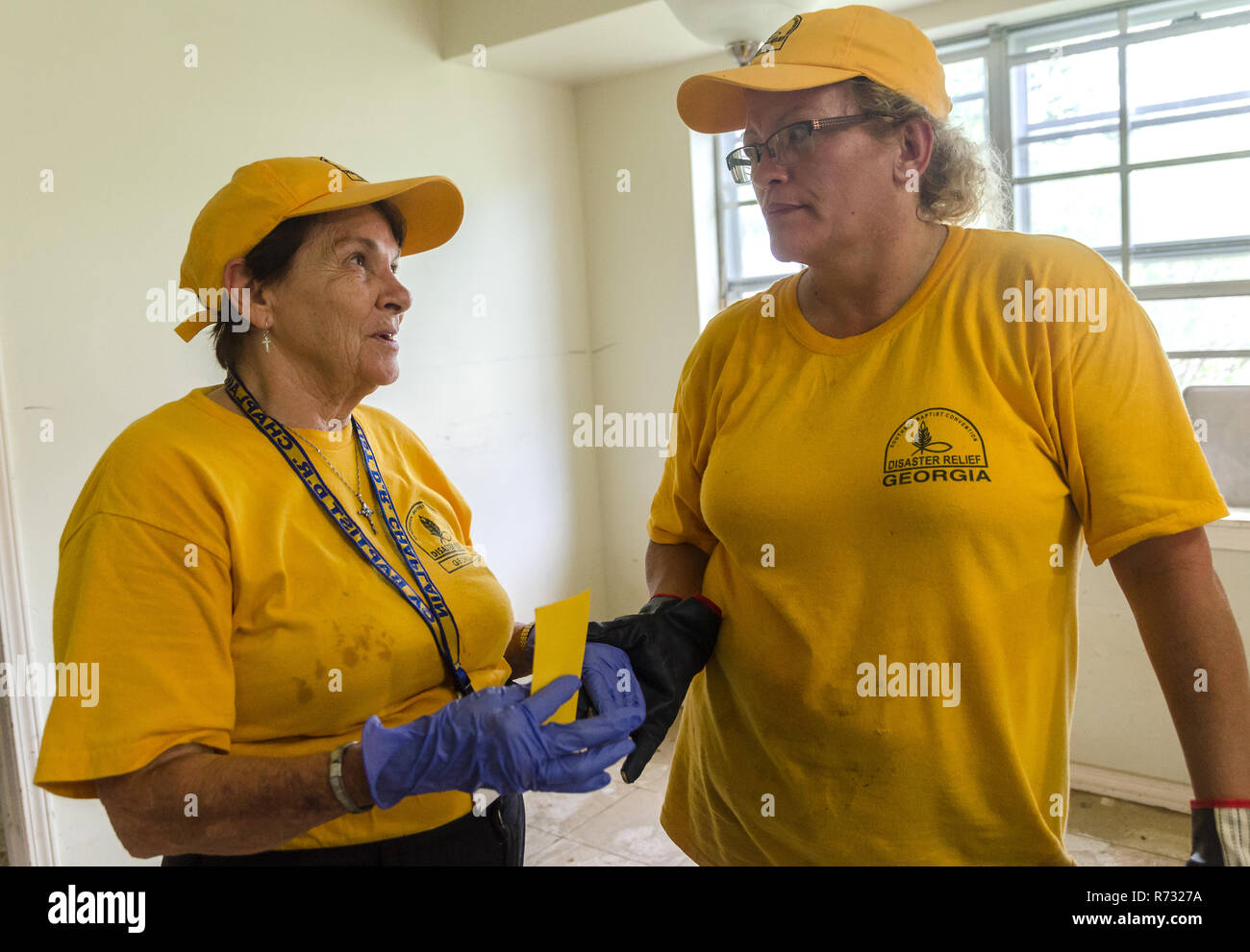 Southern Baptist Disaster Relief volunteers talk as they help clean out a flood victim's house after a flood in Denham Springs, Louisiana. - Stock Image