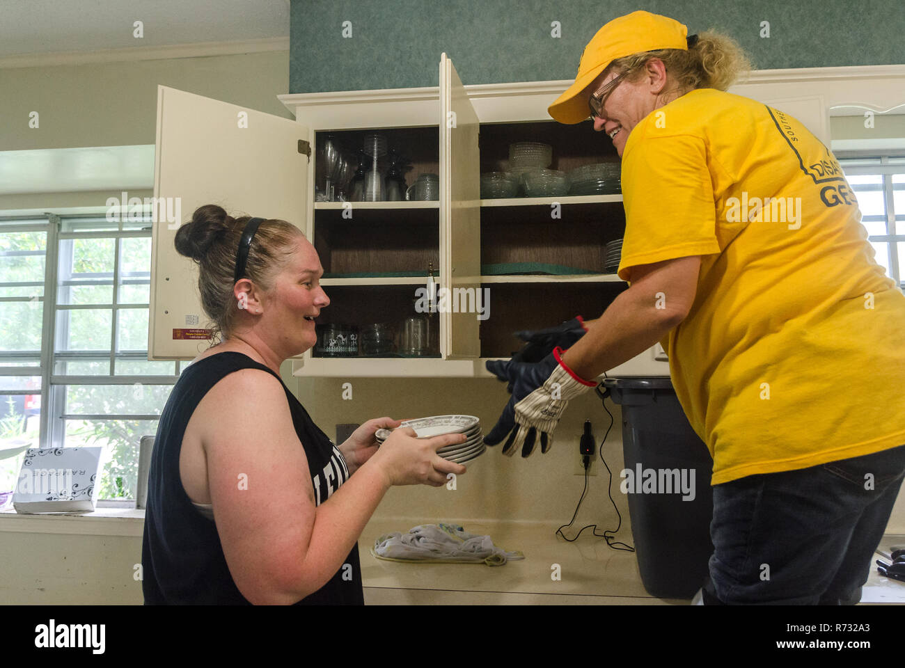 A Southern Baptist Disaster Relief volunteer helps a flood victim clean out cabinets after a flood in Denham Springs, Louisiana. - Stock Image