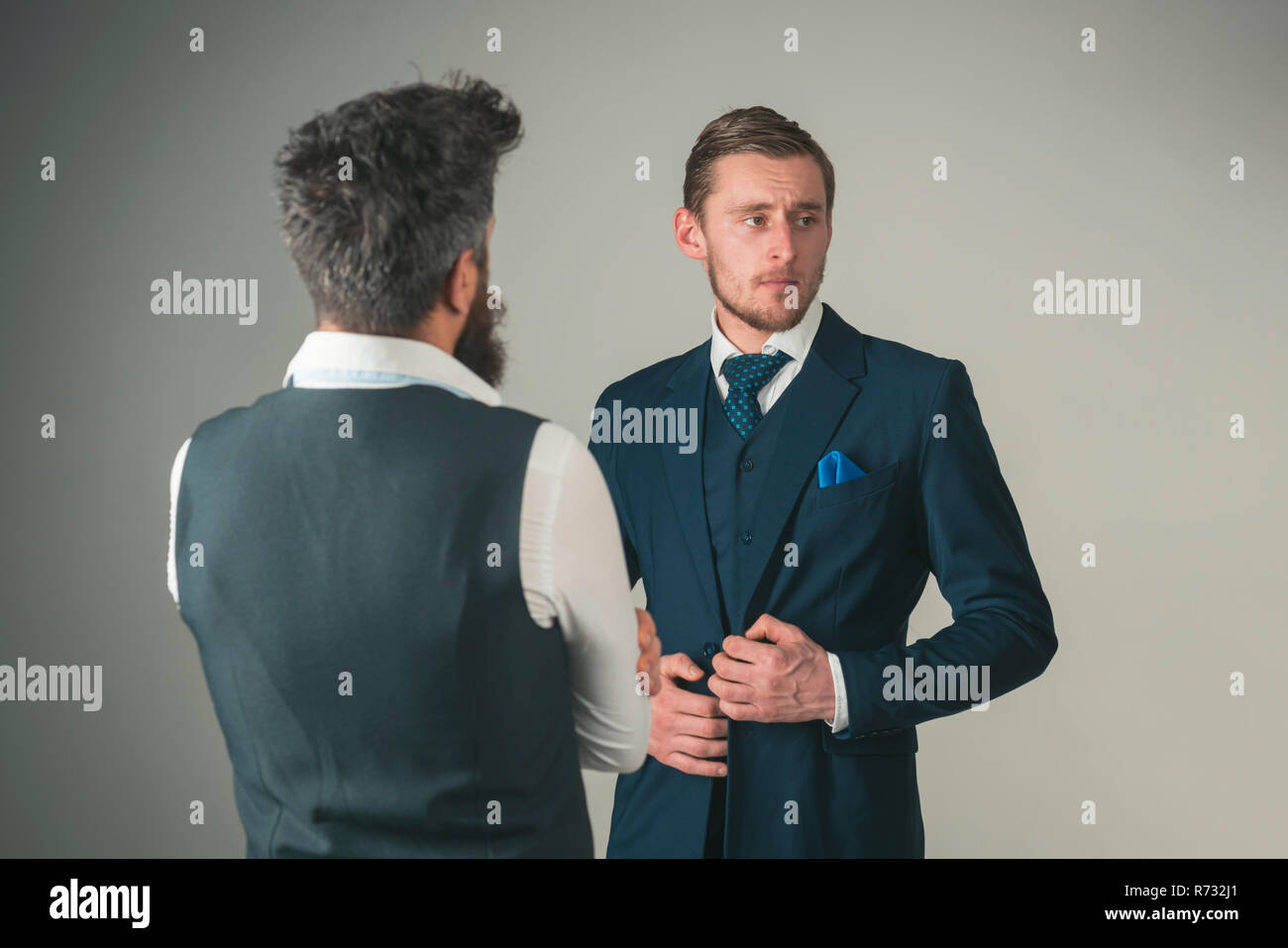 Every man should own a great suit. Fashion models in business relations. Men wear fashion business formal style. Friends in friendship relations. Bonds of friendship and cooperation among businessmen - Stock Image