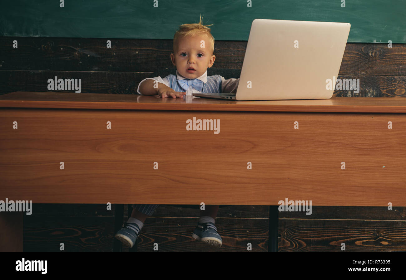 Adorable toddler learn computer knowledge in school classroom. Test of knowledge. Know how - Stock Image